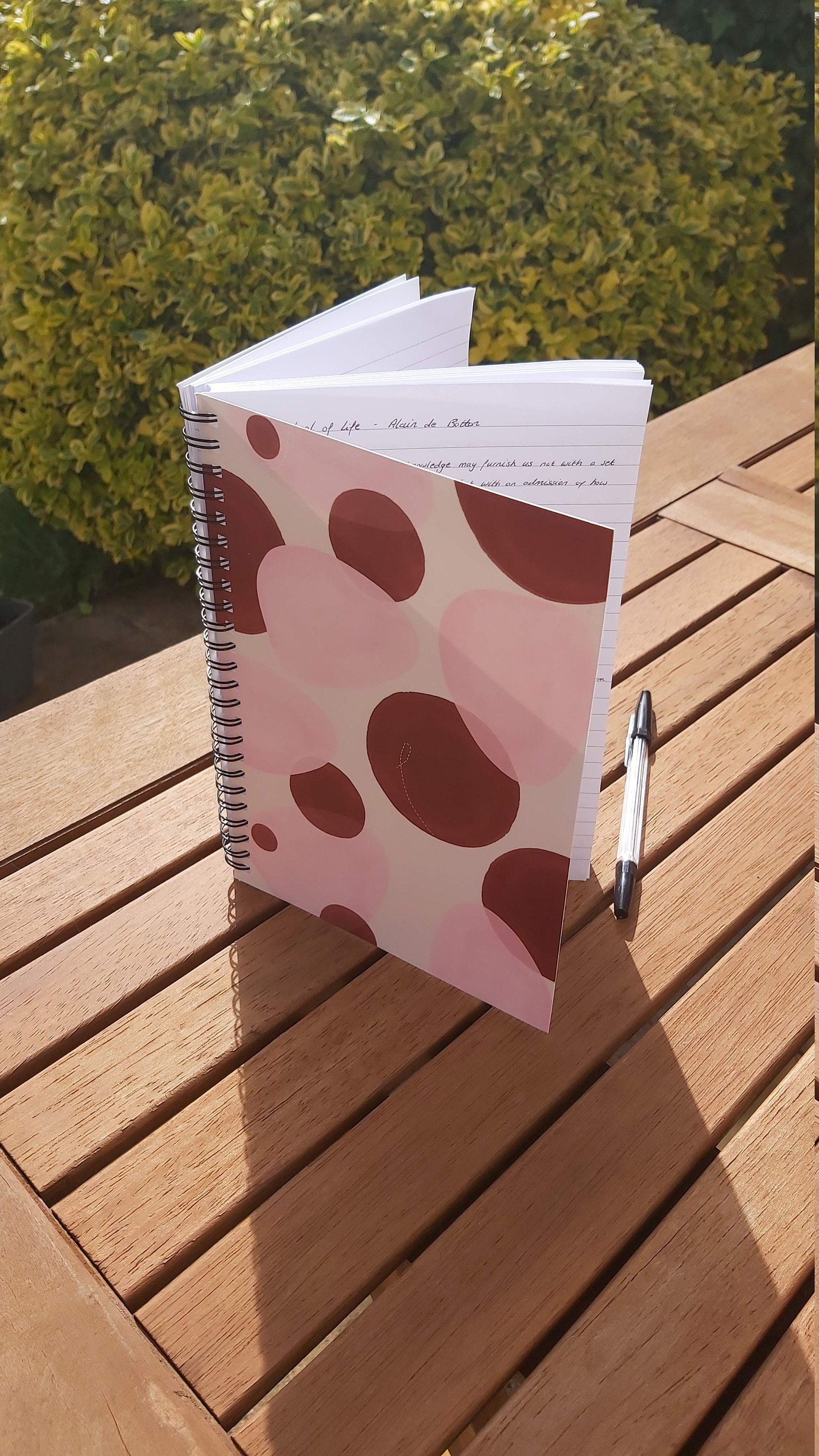 A photograph of a standing spiral-bound notebook, placed on a wooden surface with greenery behind. The notebook has a pink and red boho abstract design on the front cover