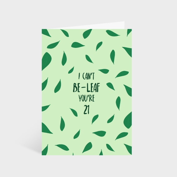 """Standing light green card with illustrated leaves dotted around, says """"I can't be-leaf it's you're 21"""" in the middle"""