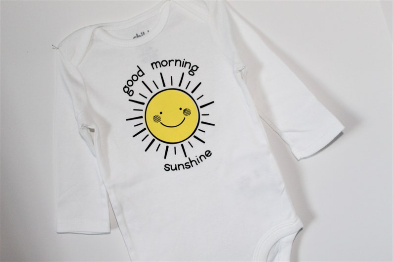 Infant boy/'sgirls/' long sleeved bodysuit with good morning sunshine lettering and yellow sun smiley face.