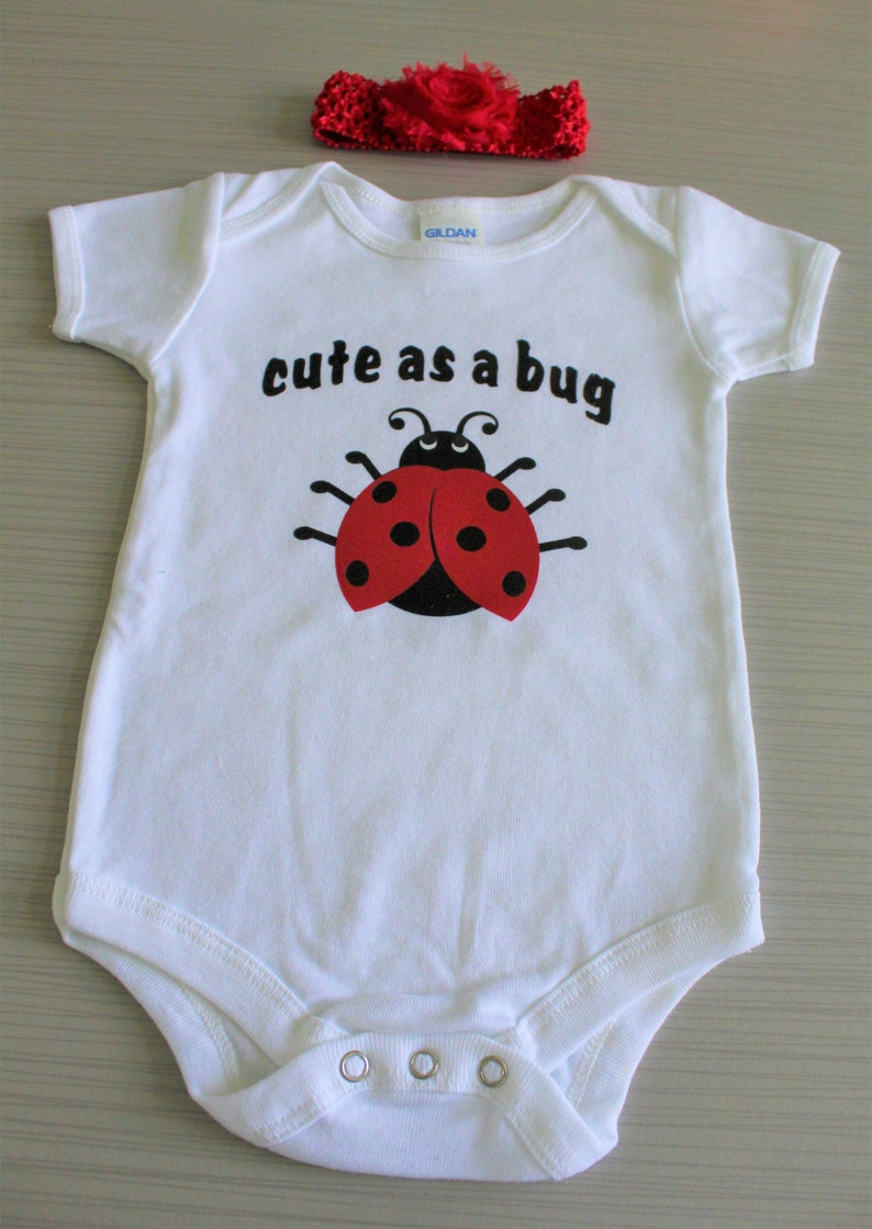 Baby girls/' white short sleeved Cute as a Bug bodysuit with a cute red and black ladybug.