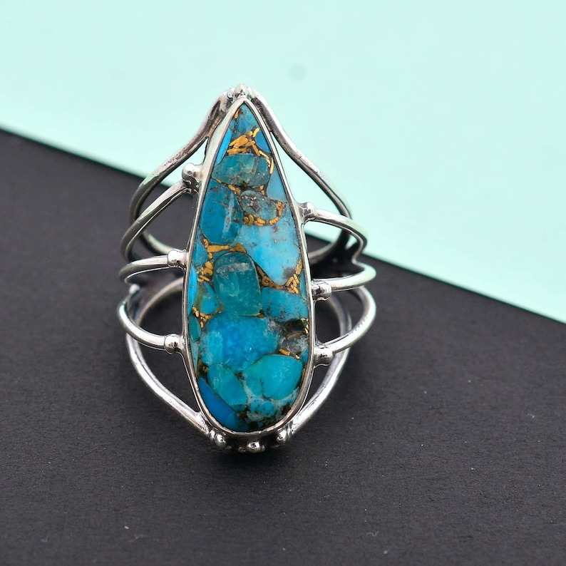 Turquoise is considered as a calming stone. Copper Turquoise teardrop multi-band ring made up of 92.5 Sterling Silver