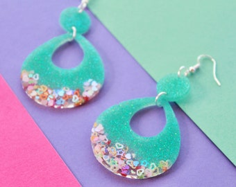 Sparkly snow white resin earring White earrings with teal accents White glitter dangles.