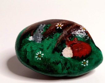 Cute painted rock paperweight of a fox and bunny in nature under a tree's roots!