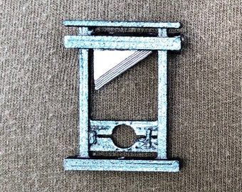 Guillotine Brooch Pin with a metallic blue finish and silver color blade