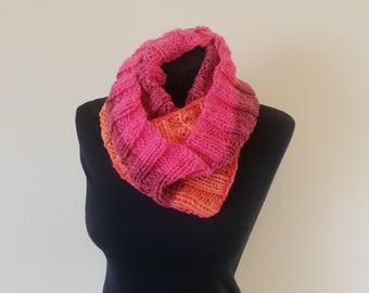 Pinky orange hand knitted cosy warm infinity scarf. Made in an acrylic mixed pink and orange wool with no seams and knitted in rib stitch