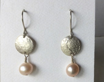 Stylish reticulated Silver disc earrings with dangling peach colored freshwater pearls. Sterling Silver ear wires