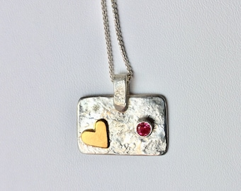 Love and friendship pendant. Golden heart and a ruby red stone on a reticulated Sterling Silver pendant.