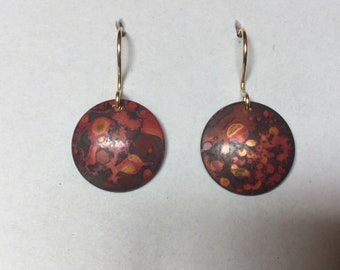 Sunset colored copper disc earrings with a heat patina. Reddish,copper, blackish sparkling colored. Formed. 14 k gold filled ear wires.