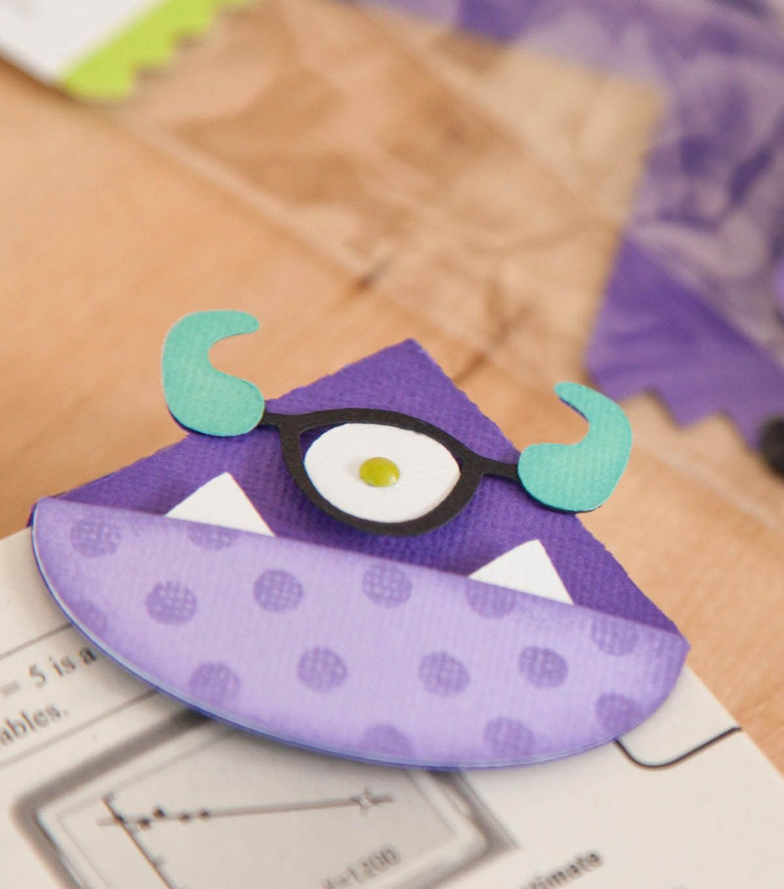 A purple monster bookmark with one eye and horns attached to the corner of an open book