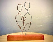 """True love. wire sculpture on 6"""" Pink Ivory, an exotic wood native to Southern Africa."""