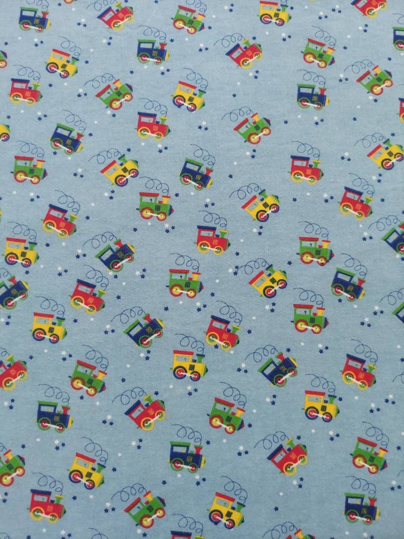 Trains in motion on Blue Flannel. Red yellow green and blue image 0