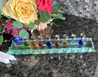 Judaica Hand made Hanukah Menorah on a clear glass base.