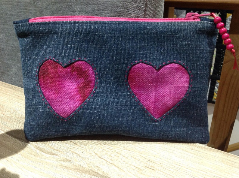 Upcycled denim zipper pouch with reverse applique hearts