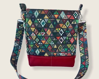 Geometric print purse made of artisan fabric and hand waxed canvas! Adjustable strap, five pockets & roomy interior, magnetic flap closure.