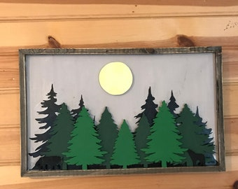framed wood with scroll saw cut tree forest. Scroll saw cut wolves, howling and walking under a full moon in a night sky