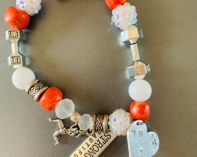 """Strong is Beautiful fitness bracelet. Buyer chooses up to three charms. The stamped charm is """"YO/OTF""""."""