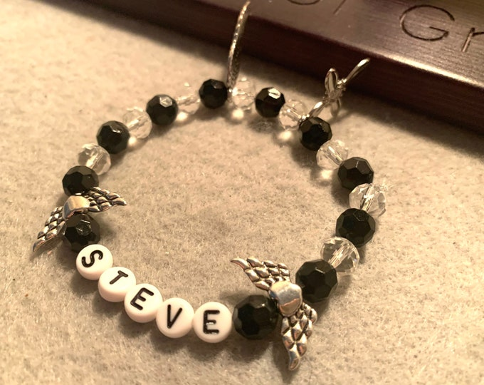 Personalized black and clear beaded stretch bracelet with angel wing beads, cross and angel wing charms