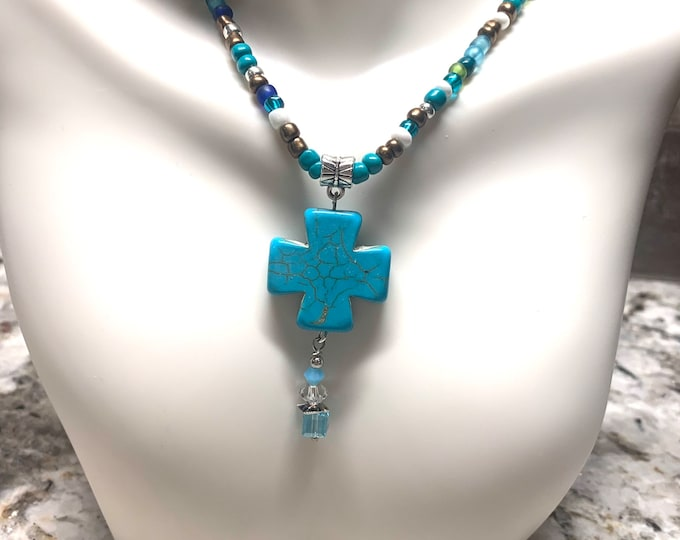 Turquoise colored cross (medium) on handmade turquoise, brown, silver beaded cord (seed beads)