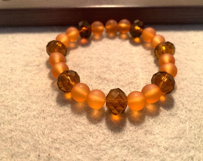 Brown and translucent orange beaded stretch bracelet