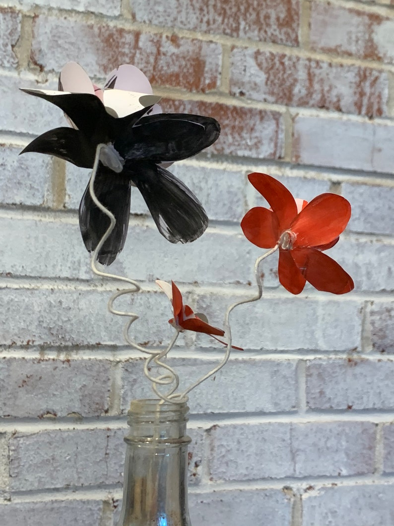 red and black paper flowers in repurposed bottle
