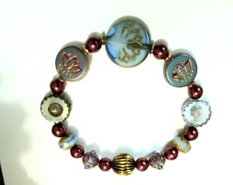 Lotus Blossom Czech glass 18mm, Laser Tatoo etched glass Lotus, Burgundy glass Pearls 6mm. Blue coin flowers, Blue rondelles, stretch cord.