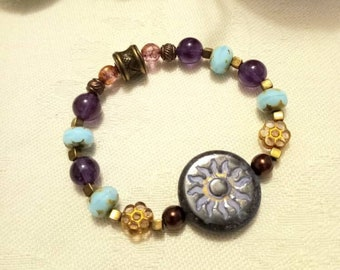 22mm Plum etched Sun bead, 8mm Amethyst, Yellow Coin Daisys, Purple 6mm Pearls, Bronze Metal bead, Czech glass turquoise on a stretch cord.