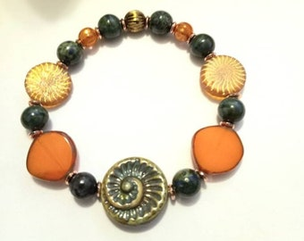 Teal Green Ammonite 18mm Czech glass. Etched Laser Tatoo beads. Tangerine Coins 15mm. Dyed Fire Agate on a stretch cord.