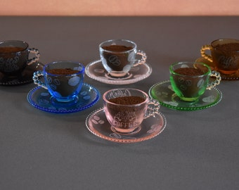 Set of colored cups with saucer with engravings related to the world of coffee