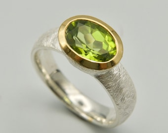 green gemstone ring with an oval, faceted peridot, ring size in silver gold