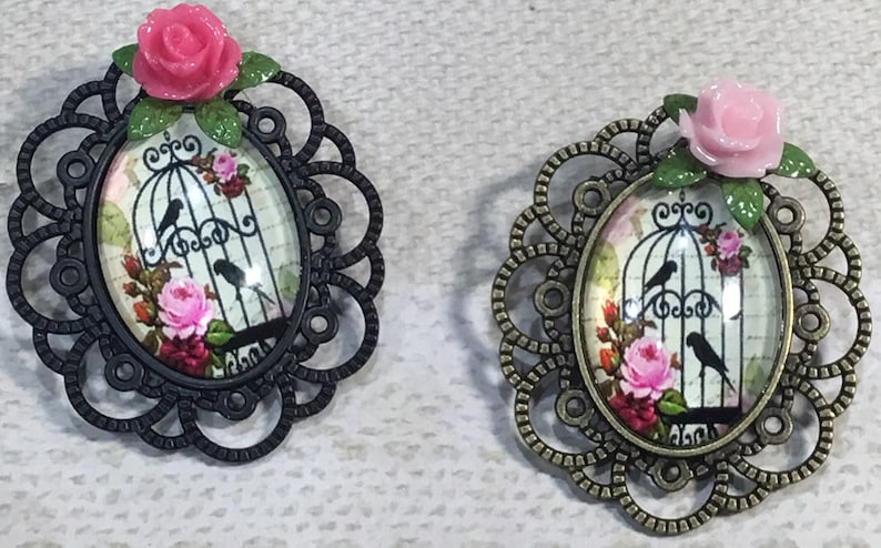 ornate bird cage pins Birdcage cabochon brooches In black filigree or antique brass bronze with resin pink rose and filigree setting.