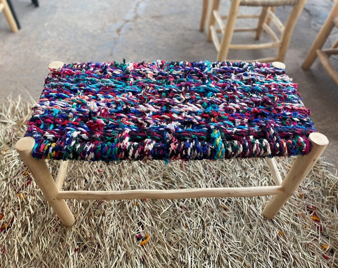 A bench made of boucherouite fabric, a Berber bench made of laurel wood and a fall of fabrics. Wooden bench