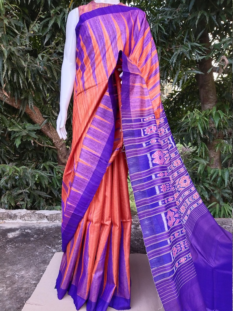 This saree comes with a blouse piece in royal blue. Handwoven orange and royal blue tussar ghicha saree with sambalpuri design in palla