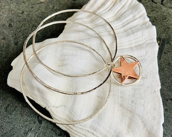 Copper star charm on a set of sterling silver bangles, a handmade and unique design.