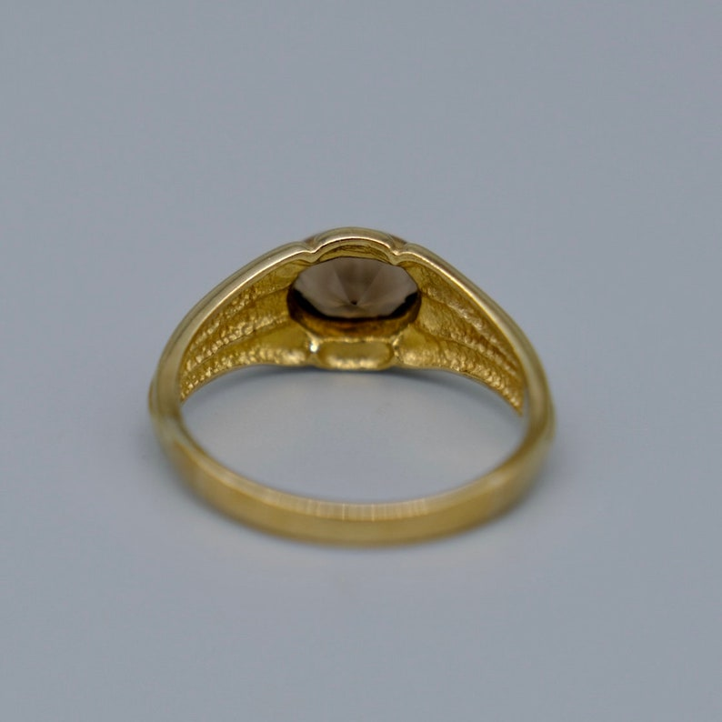 A lovely 9ct yellow gold vintage smokey topaz ring set with a single oval cut topaz in a lovely chunky gold band.