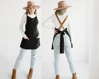 Customizable cross back apron with adjustable vegan leather straps.