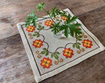 A bright and cheery square table topper with sweet floral embroideries