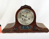 Antique oak mantel clock with ornaments.