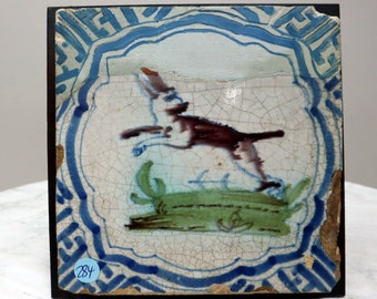 Antique tile with a colored image of a fox. In restored condition.