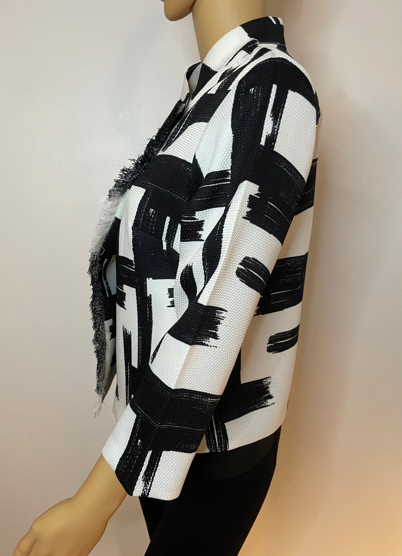 Black and white graphic print one black shiny button and snap wrap jacket Frayed off center side Cropped flare sleeves Very 60\u2019s mod!