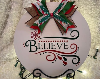 Hand painted White Believe wood sign with multi-colored bow