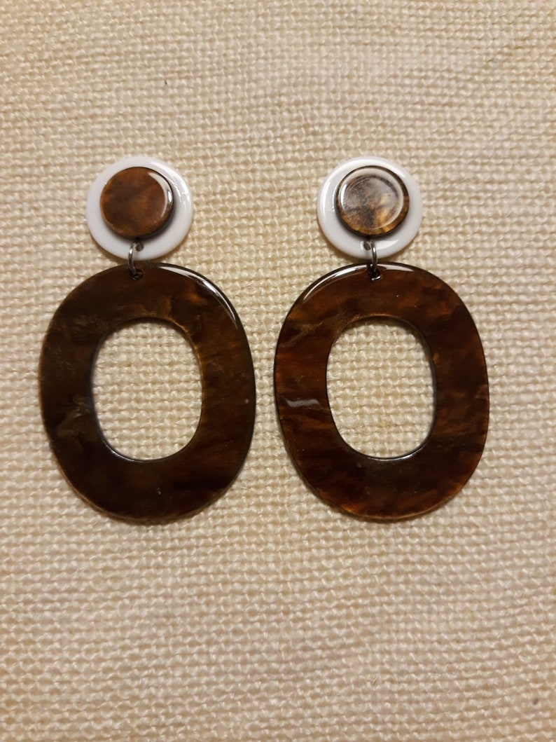 resin earrings dangling in brown and white colors