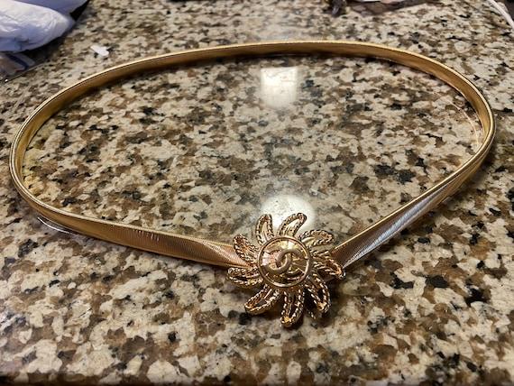 Gold toned sunburst letter stretch belt