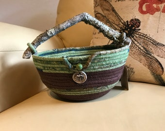Natural wood handle fabric wrapped coiled rope basket in browns and greens