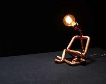 Copper pipe chilled cross legged man