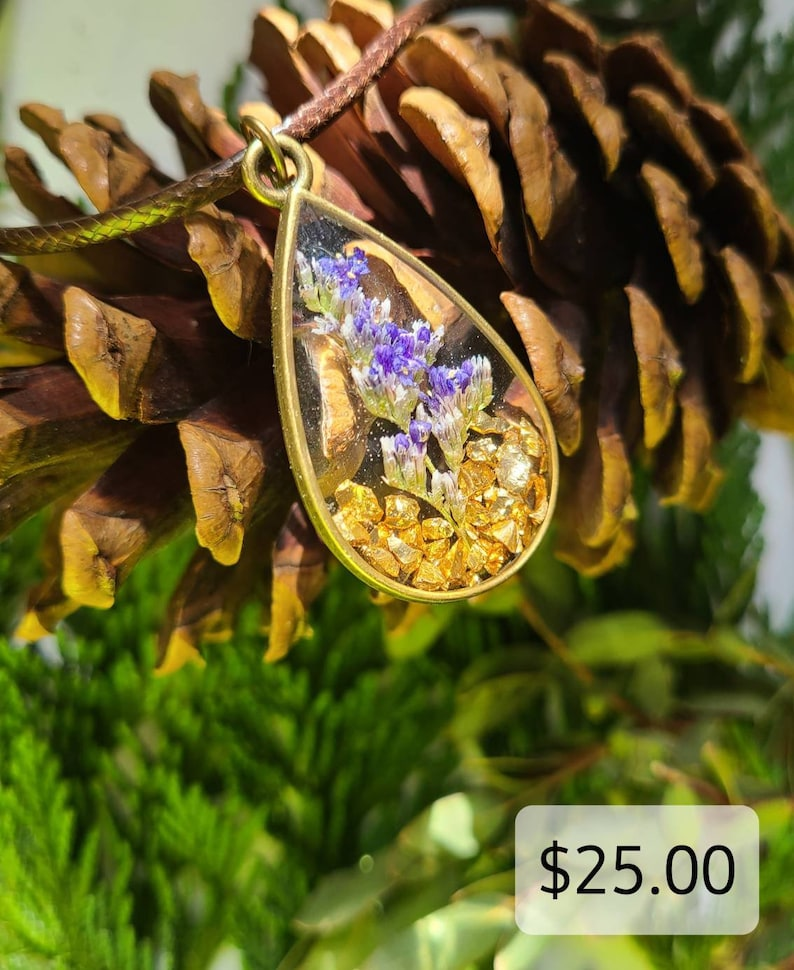 Purpleblue natural flower resin pendant with gold colored rock pieces