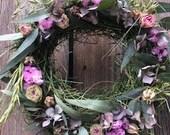 Hay wreath with dried roses, lilac, nigella, barley, oats, hydrangeas, eucalyptus