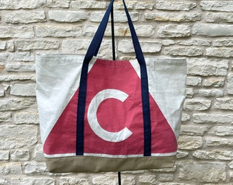 Recycled sailcloth bag with vintage red Catalina logo, tan canvas bottom, navy blue webbing handles, external pocket, metal D-ring & clasp