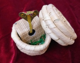 Real cobra replica in a bamboo hay basket made by snake charmers who work part time in the bamboo field
