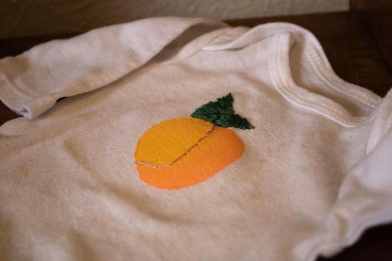 Newborn white onesie hand painted and embroidered peach