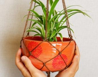 Hanging orange planter with brown macramé